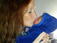 An old photo of Gail kissing a baby.