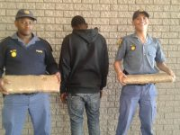 Constable Hlangi Tayi Tayi and Constable Daryll Vink on either side of the foreign national, holding the stash. Photo: Provided